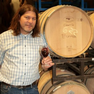 Michael Barreto standing in front of wine barrels with a glass of wine
